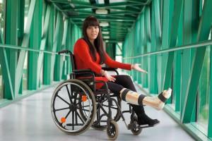 Junge Frau mit Gipsbein sitzt in einem Rollstuhl